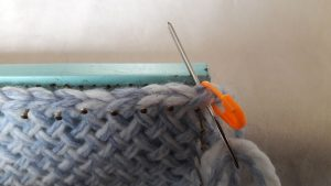 Put needle through 2 loops of the first stitch